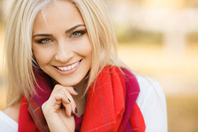 Smiling woman with blond hair, blue eyes and bright red scarf
