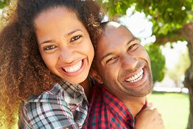 Laughing couple with woman hugging man from behind