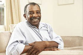 Smiling man in long-sleeved shirt crossing arms and sitting on couch