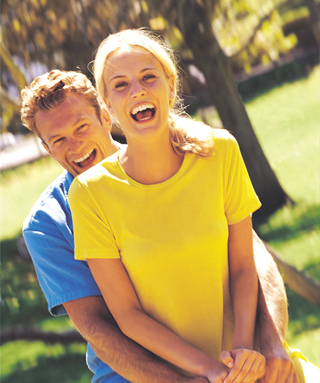 A young, blonde couple laughs outside in the sunshine.
