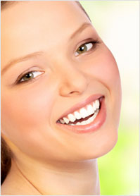 A young girl with brilliantly white teeth smiles happily.